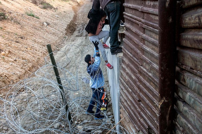 Central American migrants crossing the border fence from Tijuana in Mexico to San Diego County in the US on Thursday.