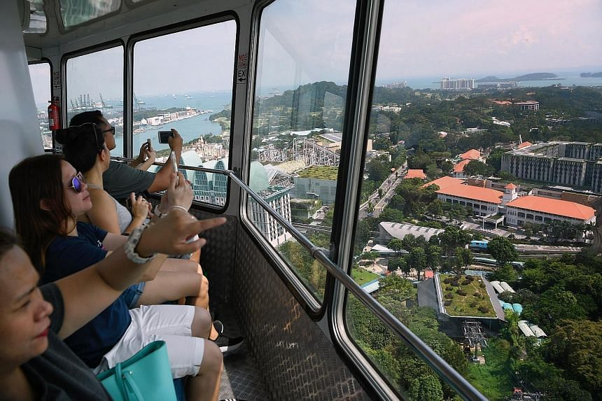 Clockwise from main photo: The Tiger Sky Tower, located at Imbiah Lookout on Sentosa, on its last day of operations yesterday. Visitors enjoying the views from inside the rotating observatory tower. In August last year, the ascending gondola stopped