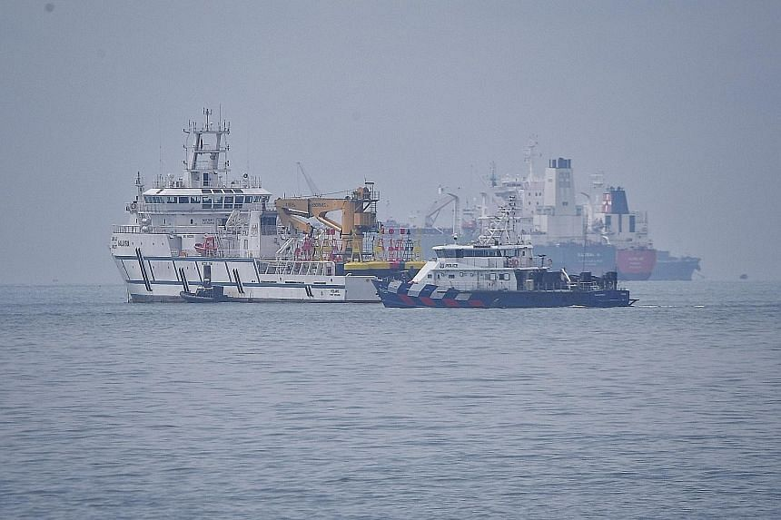 A Singapore Police Coast Guard vessel passing a Malaysian government vessel (left) in Singapore's territorial waters off Tuas on Dec 6. A territorial spat unfolded after Malaysia unilaterally extended the Johor Baru port limits.