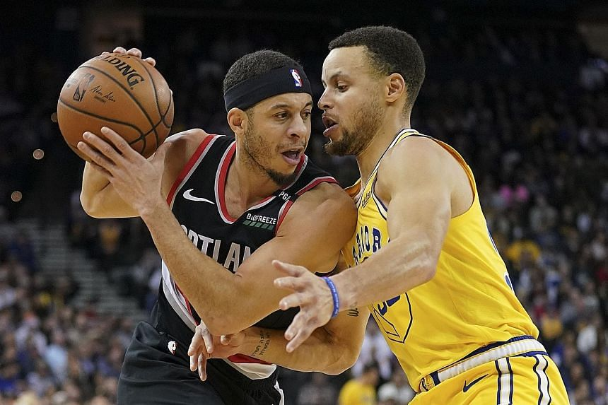 Portland Trail Blazers' Seth Curry being defended by his brother and Golden State Warriors guard Stephen Curry at the Oracle Arena on Thursday. Portland shocked the NBA champions with a 110-109 overtime win to hand the hosts their fifth home loss thi