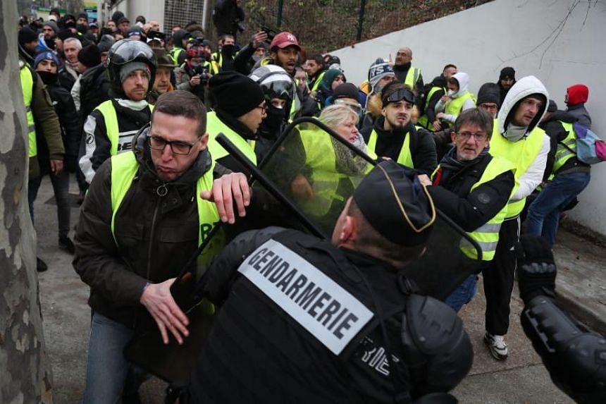 """""""Yellow vest"""" protesters clash with police officers in Paris on Dec 29, 2018."""