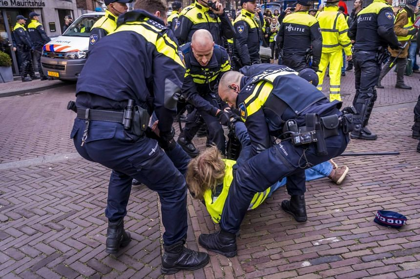 Police arrest protesters wearing yellow vests demonstrating in The Hague.