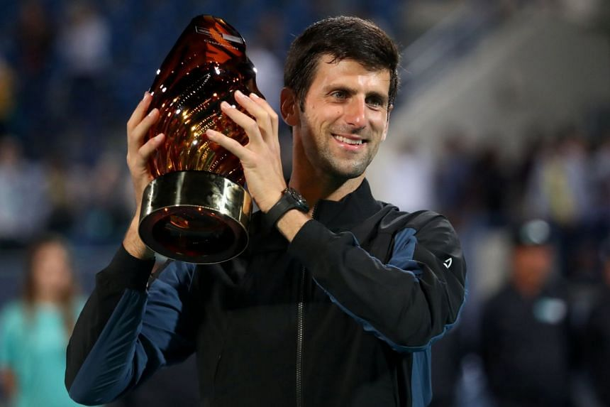 Serbia's Novak Djokovic celebrates with the trophy after defeating South Africa's Kevin Anderson.