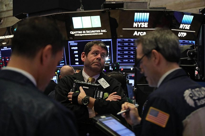 Traders on the floor of the New York Stock Exchange on Dec 6 when the Dow Jones Industrial Average fell over 400 points in morning trading. Escalating US-China trade tensions sent waves of volatility throughout the markets in the second half of this year,
