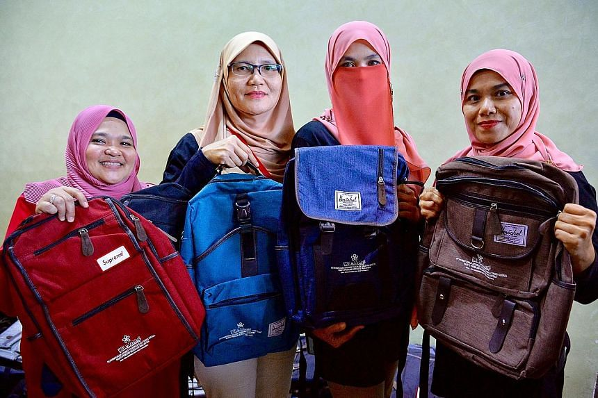 Parti Pribumi Bersatu Malaysia workers showing the different Herschel backpacks - with the party logo emblazoned on them - given to select central delegates at the party's annual general assembly in Putrajaya yesterday.