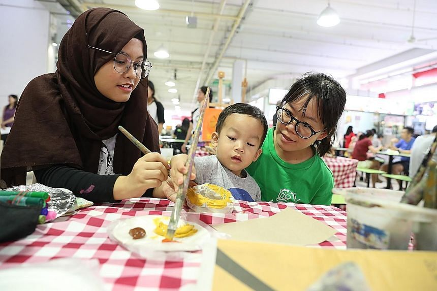 Senior Minister of State for the Environment and Water Resources Amy Khor (left) and Hougang resident Lau Heng Mui being assisted by event organiser and Art Chamber founder Fay Tan, at an art jamming session held at Ci Yuan Hawker Centre yesterday as
