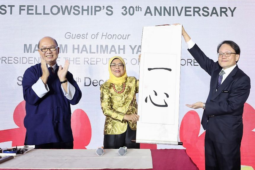 """President Halimah Yacob holding up her Chinese calligraphy,which means """"one heart"""", flanked by calligrapher Lim Joon Hiang (left) and Buddhist Fellowship president Lim Phang Hong at the Buddhist Fellowship's 30th Anniversary dinner on Dec 30, 2018."""