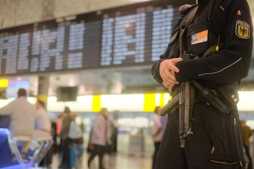 An armed police officer patrols at the airport in Hanover on Dec 29, 2018 after flight operations were suspended.