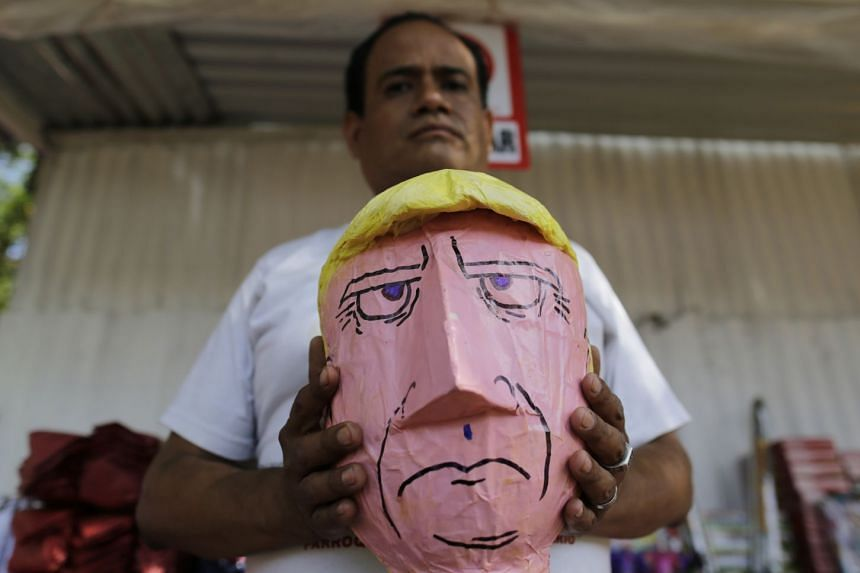 A man shows his hand-made Donald Trump puppet in Nicaragua, where such effigies are traditionally burned on Dec 31 as a way of saying goodbye to the old year and welcoming the new one.