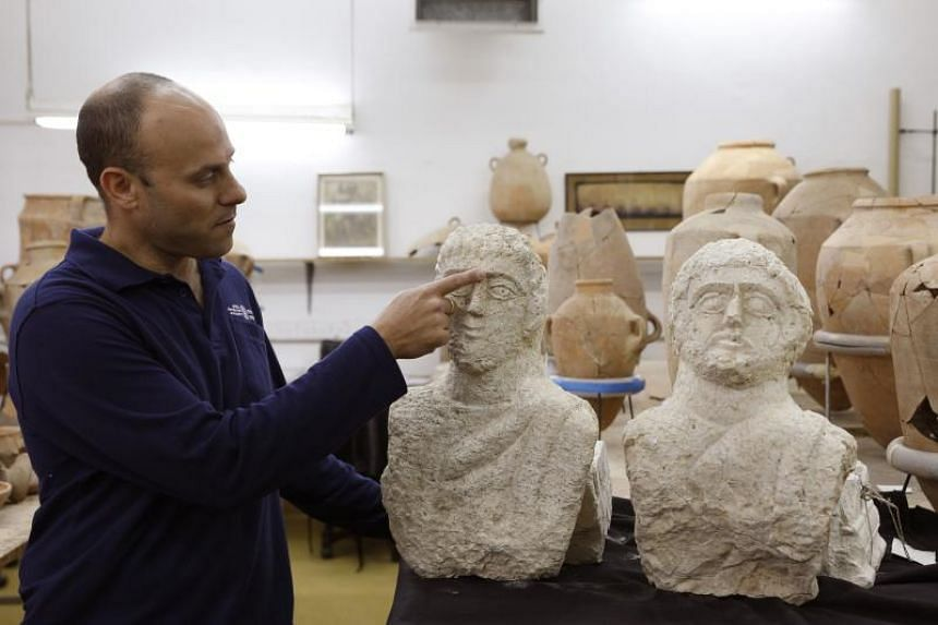 Israeli archeologist Eitan Klein of the Israel Antiquities Authority displaying a pair of Roman busts that were discovered by an Israeli woman walking near some ancient ruins in the city of Beit Shean.