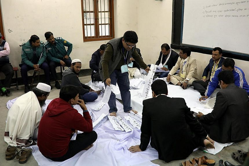 Presiding officers starting to count ballots at a voting centre in Dhaka yesterday after polling ended. There are 300 parliamentary constituencies in Bangladesh. An army vehicle patrolling the streets of Dhaka yesterday as clashes broke out across th