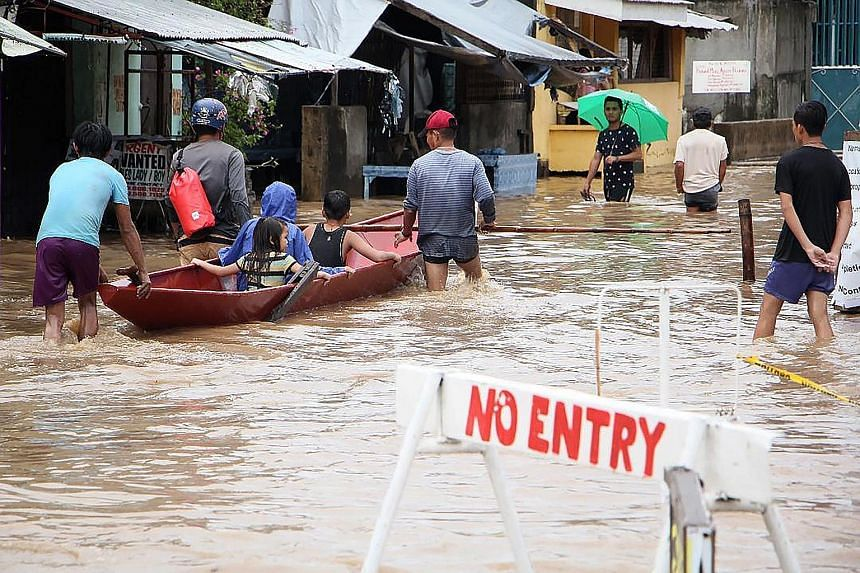 People wading through a flooded street yesterday in the town of Baao in Camarines Sur province, where casualties from the weekend storm included a father and his son, who were buried alive in a landslide. A destroyed house in Daet, in Luzon's Camarin