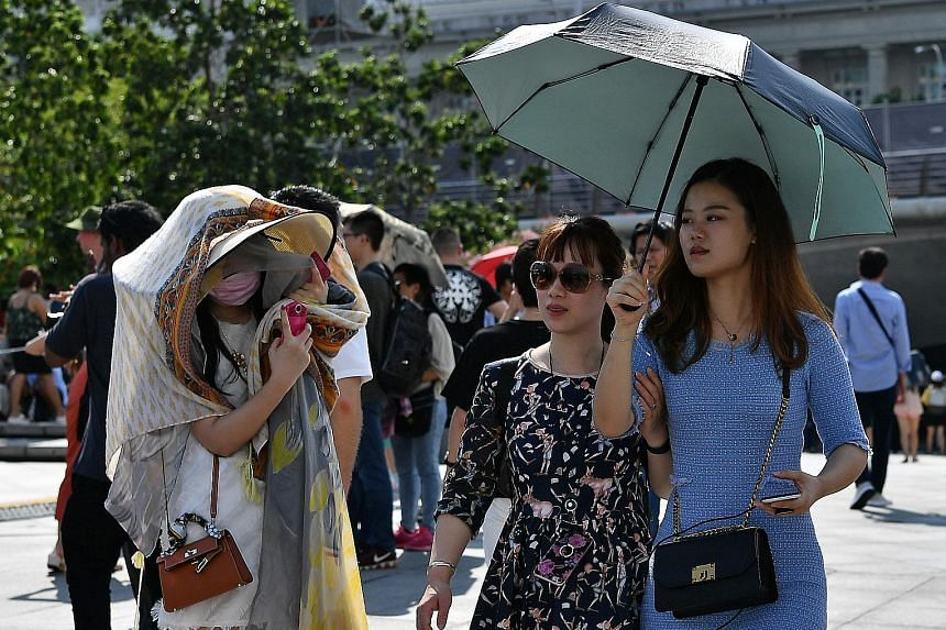 Scorching heat on the last Sunday afternoon of the year yesterday saw Singaporeans and tourists alike seeking shelter. Sunshades and a sea of umbrellas were a common sight at parks and open spaces around the island. At Merlion Park (above), two women
