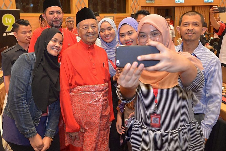 Members of the Malaysian media taking a wefie with PPBM chairman Mahathir Mohamad when he visited the media centre at his party's annual assembly yesterday.