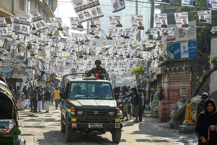 Bangladeshi army personnel patrolling a street adorned with election posters near a polling station in Dhaka yesterday. Election-related violence killed 17 people yesterday, a police spokesman said.