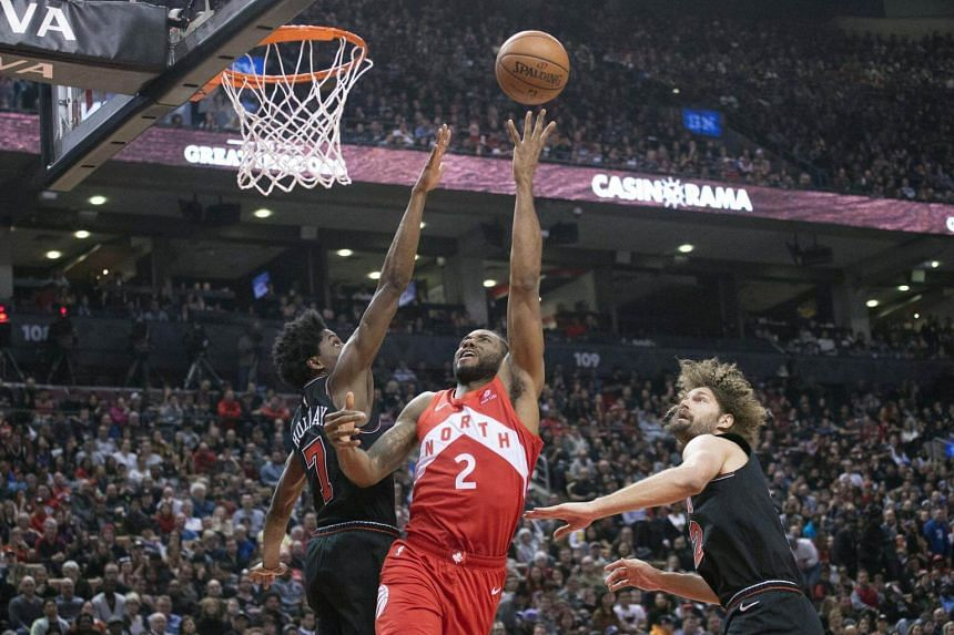 Toronto Raptors forward Kawhi Leonard (centre) drives to the basket between Chicago Bulls' Justin Holiday and Robin Lopez during the second quarter at Scotiabank Arena on Dec 30, 2018.