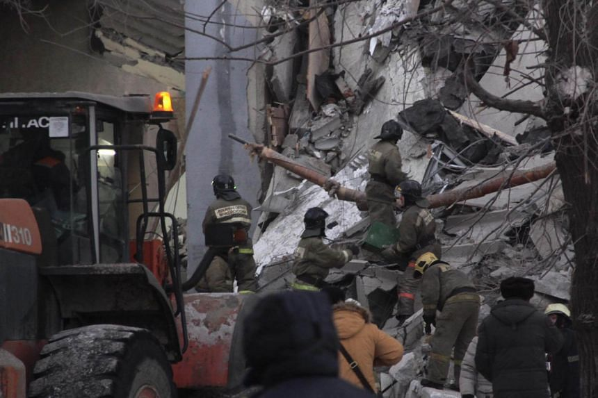 Russian rescue workers remove debris after a gas explosion in an apartment building in the city of Magnitogorsk, Russia, on Dec 31, 2018.