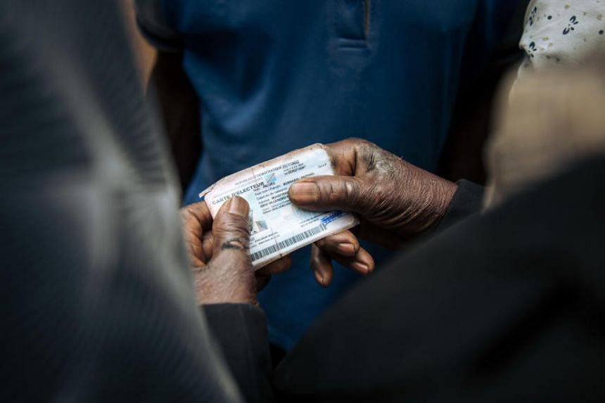 A man holds his voter card at a symbolic polling station on Dec 30, 2018.