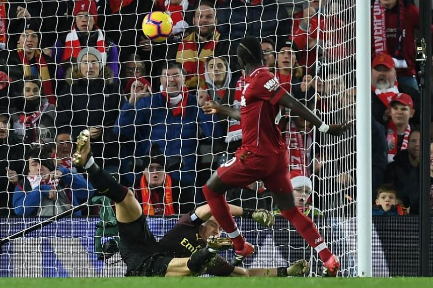 Liverpool's Senegalese striker Sadio Mane (right) scores his team's third goal past Arsenal's German goalkeeper Bernd Leno during the English Premier League football match between Liverpool and Arsenal at Anfield in Liverpool, north west England on D