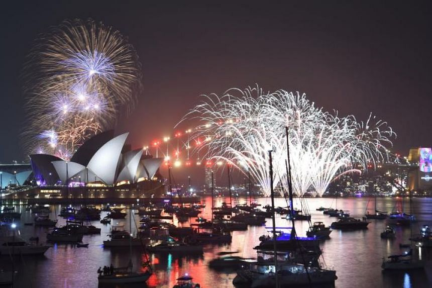 New Year's Eve fireworks explode over the Harbour Bridge and Opera House before the main midnight event in Sydney on Dec 31, 2018.