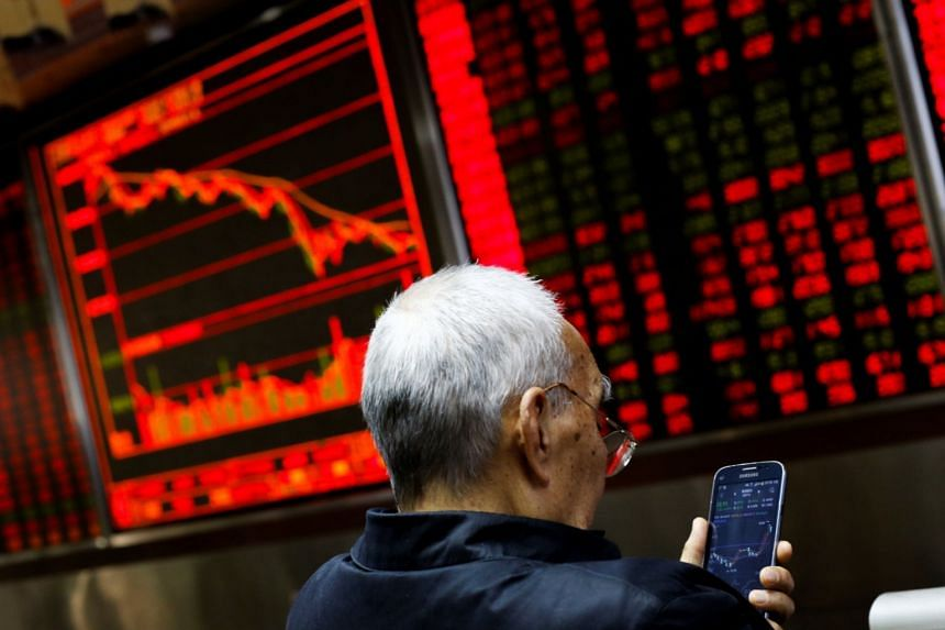 An investor sits in front of a board showing stock information at a brokerage office in Beijing, China, on Dece 7, 2018.