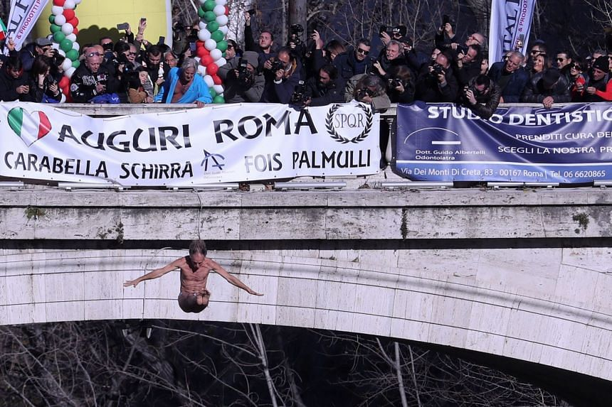 Marco Fois dives into the Tiber River from the Cavour bridge, as part of traditional New Year celebrations in Rome.