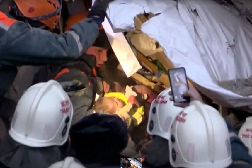 A video still shows a rescuer carrying an 11-month-old child found alive in the rubble of a Russian apartment block.
