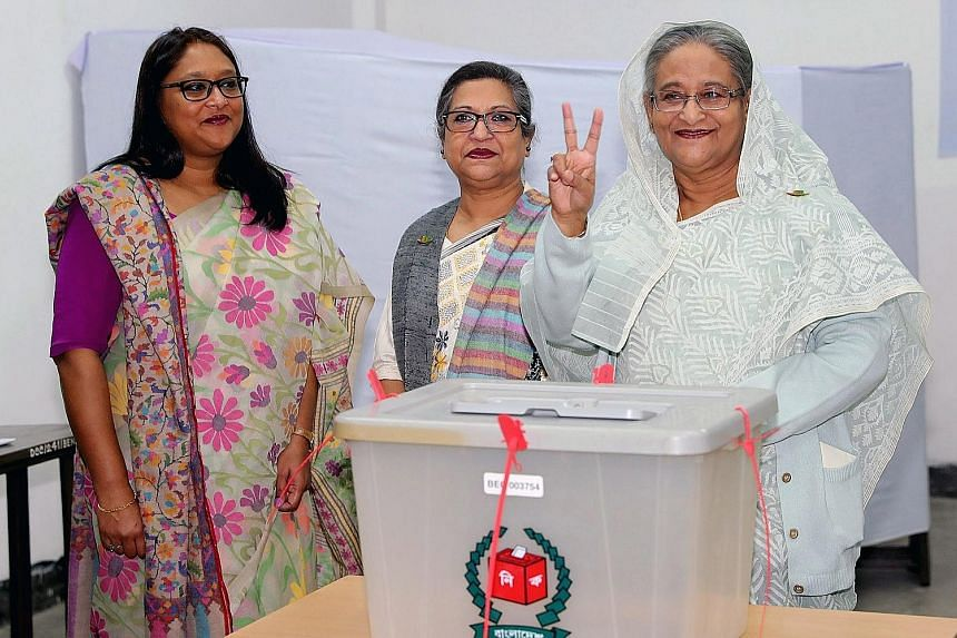 Bangladeshi Prime Minister Sheikh Hasina flashing the victory sign after casting her vote, accompanied by her daughter Saima Wazed Hossain (left) and sister Sheikh Rehana, at a polling station in Dhaka on Sunday.