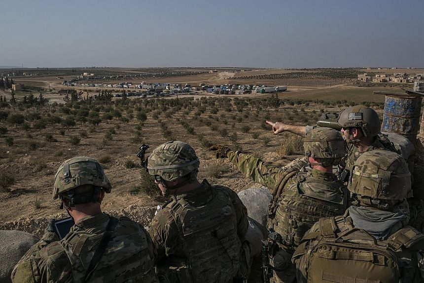 """US Special Forces soldiers at a front line outpost outside Manbij, Syria, last February. The Pentagon says it is considering plans for a """"deliberate and controlled withdrawal"""" from Syria."""
