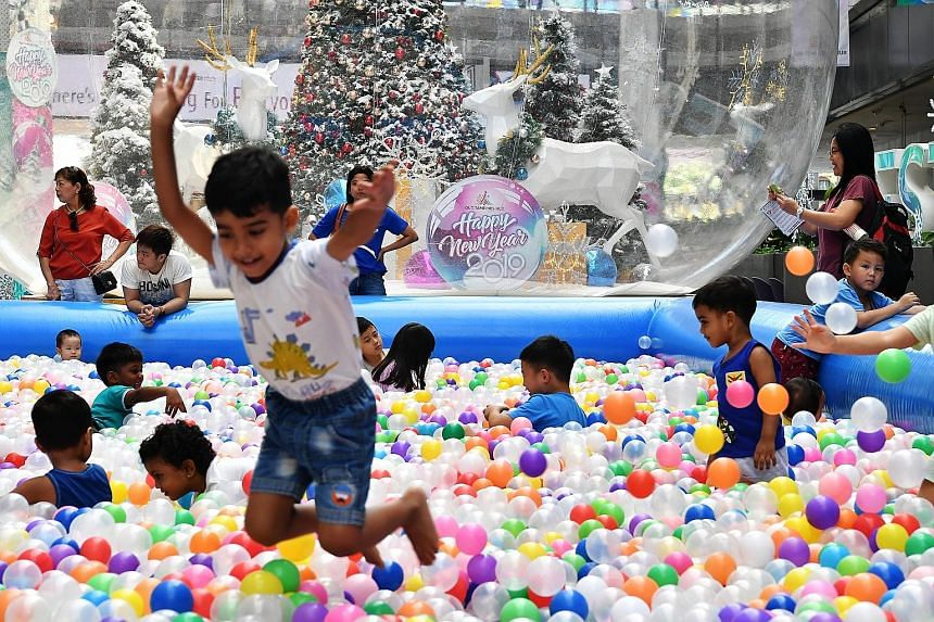 Children at Our Tampines Hub having fun yesterday in a giant ball pit, one of several free fringe activities organised ahead of the new year. Other events included free movie screenings and a food bazaar. Over at Marina Bay, hundreds of thousands of