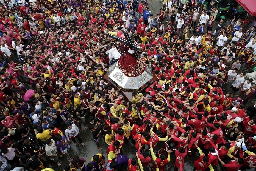 Thousands of Catholics jostled to get closer to the Black Nazarene statue during a thanksgiving procession in Manila yesterday. Every year, before the start of the New Year, barefoot devotees in the Philippines gather for the procession of the Black