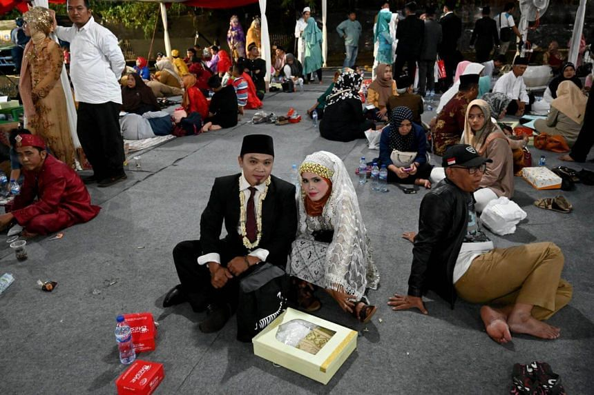 Wedding couples wait for their turn to be solemnised as they join over 500 other pairs in a mass wedding event in Jakarta, on Dec 31, 2018.