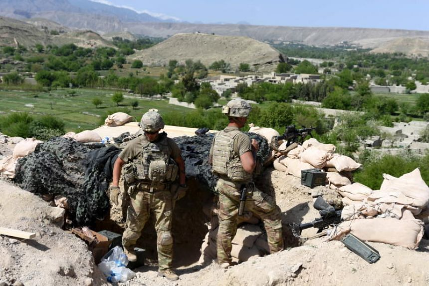 US soldiers take position during an operation against Islamic State militants in the Khot district of Afghanistan on April 11, 2017. The Trump administration has not denied reports that the US plans to pull out almost half of the 14,000-strong force