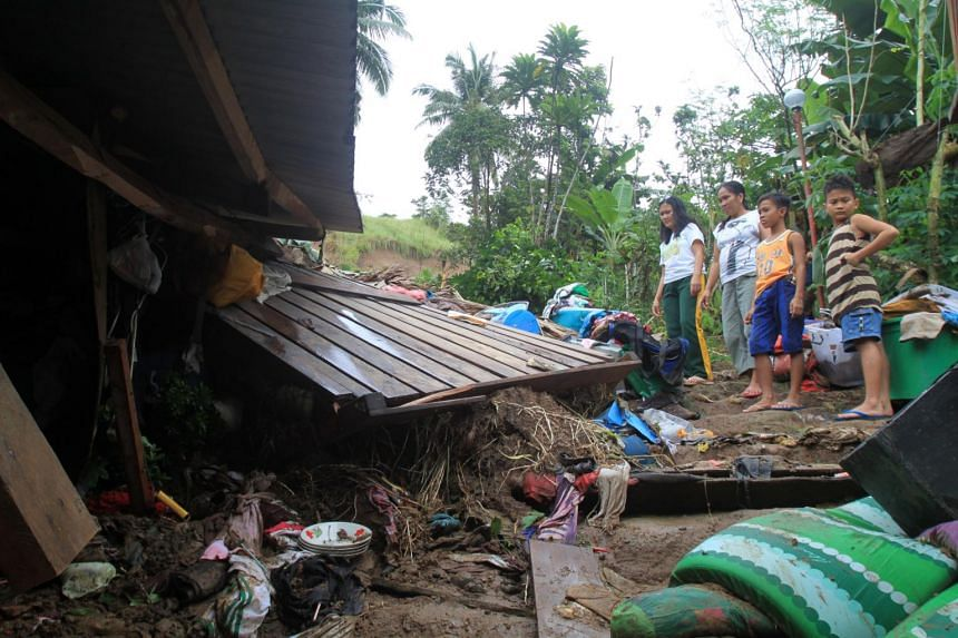 Residents look over their damaged home at the landslide-hit community in Bulan Sorsogon province Philippines on Dec 29 2018