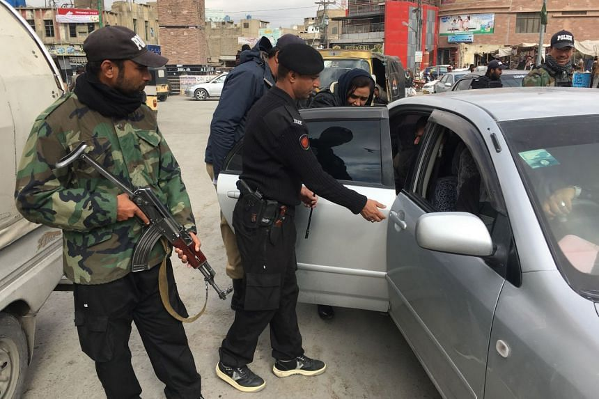 Pakistani officials check vehicles in Quetta, amid enhanced security following the attack.