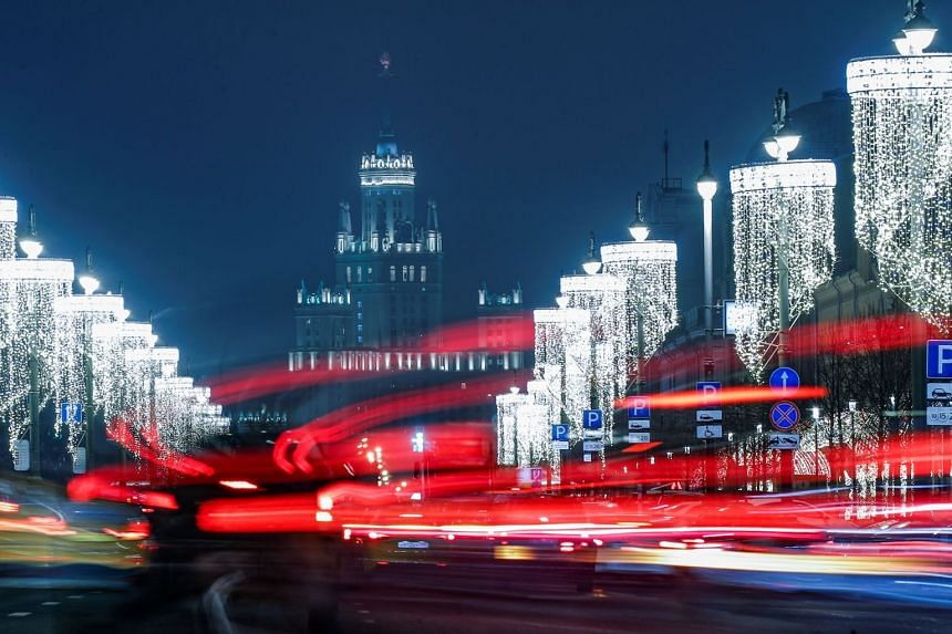 Cars pass along a street decorated with Christmas and New Year lights in Moscow, Russia.