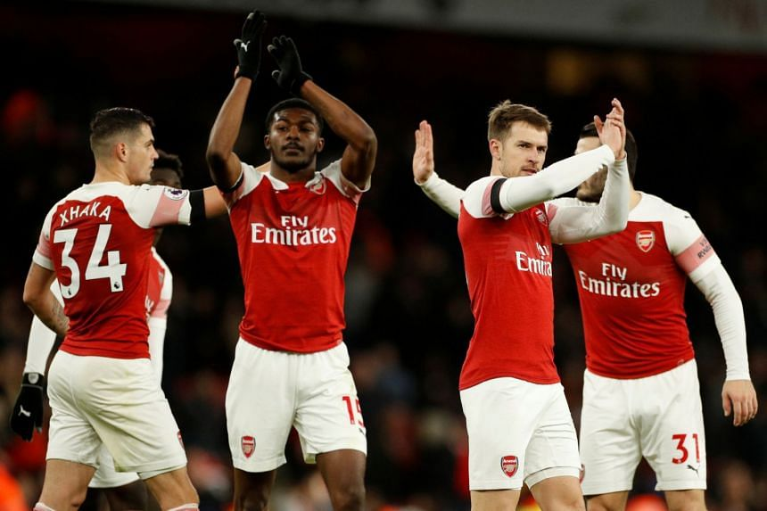 Arsenal's Aaron Ramsey, Ainsley Maitland-Niles and team mates celebrate after the match.