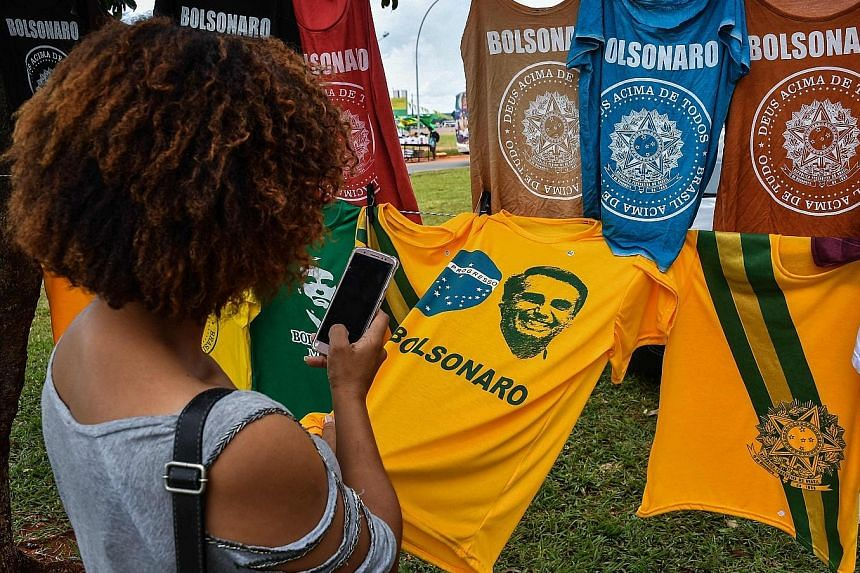 T-shirts with the image of new Brazilian President Jair Bolsonaro on display for sale in Brasilia. Inaugurated yesterday, Mr Bolsonaro has vowed to eradicate graft, crack down on crime and open up Brazil's protectionist economy to the free market.