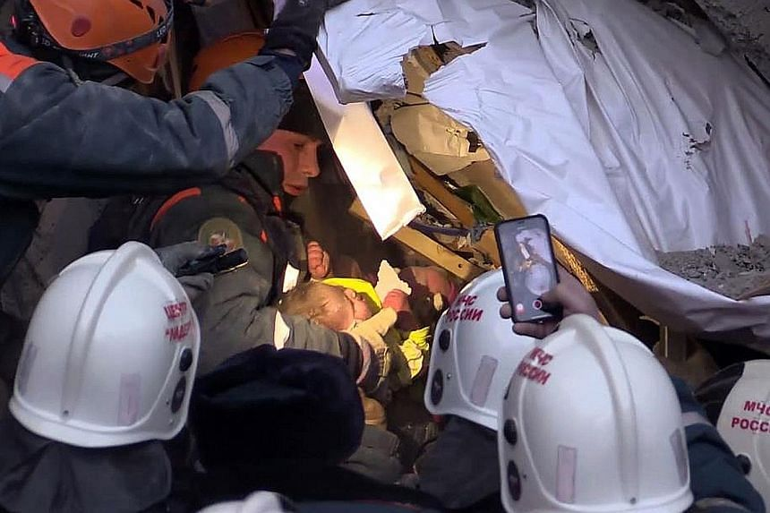 Emergency officers rescuing a baby who was found alive yesterday after being trapped under the rubble of a Russian apartment block for 35 hours. The block partially collapsed in an explosion. The 11-month-old has been diagnosed with serious freezer b