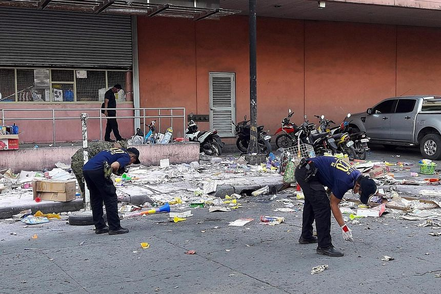 Police gathering evidence at the site of Monday's blast outside a shopping mall in Cotabato city, southern Philippines.