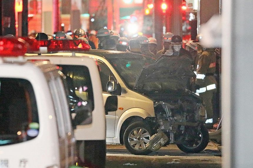 Police inspecting the rented car that Kazuhiro Kusakabe drove into a group of pedestrians in Harajuku's Takeshita Street. The car came to a stop when Kusakabe crashed into a building. It bore an Osaka licence plate and carried a tank with 20 litres o