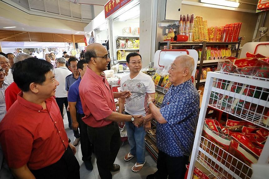Above: Vegetable stall helper Tay Quek Hua, 70, helping a customer pack selected vegetables from his stall. Left: DPM Tharman stopping by at the incense stall of Mr Chian Kwang Huat (in white), 45, and shaking hands with Mr Tan Chai Poh, 76, a freque