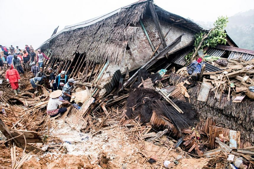 Rescue workers searching for victims yesterday near a collapsed house following landslides in Sukabumi regency in Indonesia's West Java province. Heavy rain in West Java and parts of the Philippines caused landslides and heavy flooding in the new yea