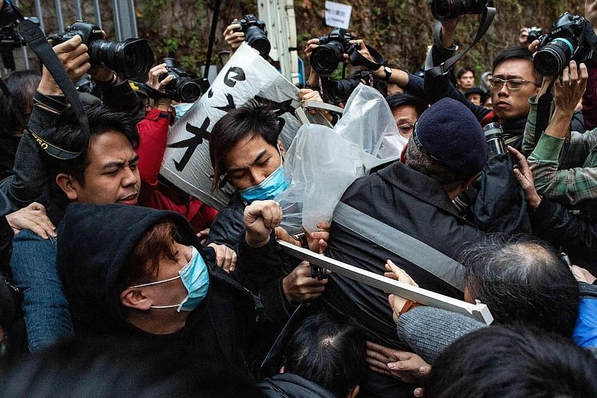 Protesters and guards clashing in Hong Kong during yesterday's pro-democracy rally. Police said some 3,200 people attended the march at its peak, while organisers gave a higher figure of 5,500 people.