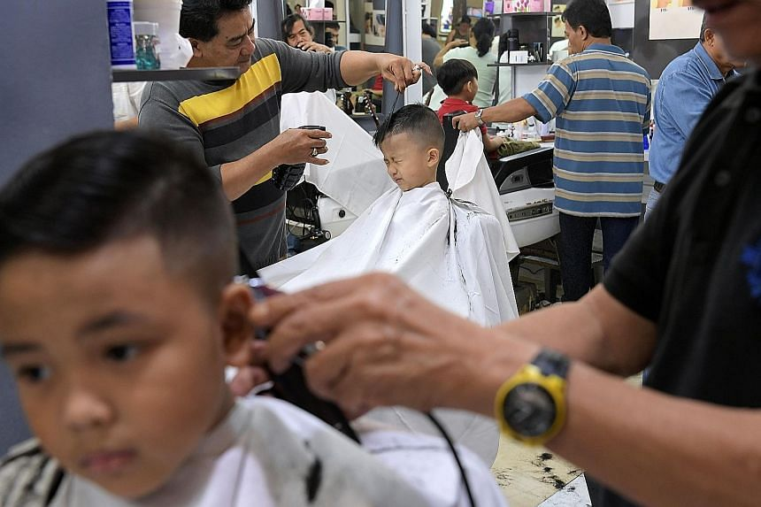 Four-year-old Jaime Chen (above) sits in a toy car at the EC House salon while getting a haircut at Compass Point in Sengkang. She is starting K1 classes in kindergarten today. Meanwhile, at the Sri Nada barber shop (right) in the same mall, six-year