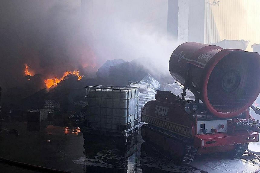 Above: Singapore Civil Defence Force (SCDF) officers using water jets to contain the fire. Far left and left: SCDF deployed 13 emergency vehicles and about 55 firefighters. At the height of the operation, eight water jets, foam and an unmanned firefi