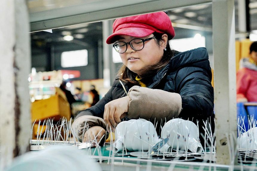 Workers produce lightbulbs that will be exported to the US at a factory in Wannian in China's central Jiangxi province.