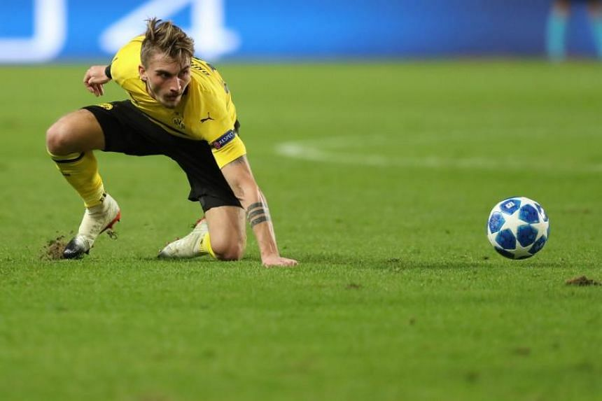 Dortmund's US midfielder Christian Pulisic falls as he eyes the ball during the UEFA Champions League Group A football match between Monaco and Dortmund at the Louis II stadium in Monaco, on Dec 11, 2018.