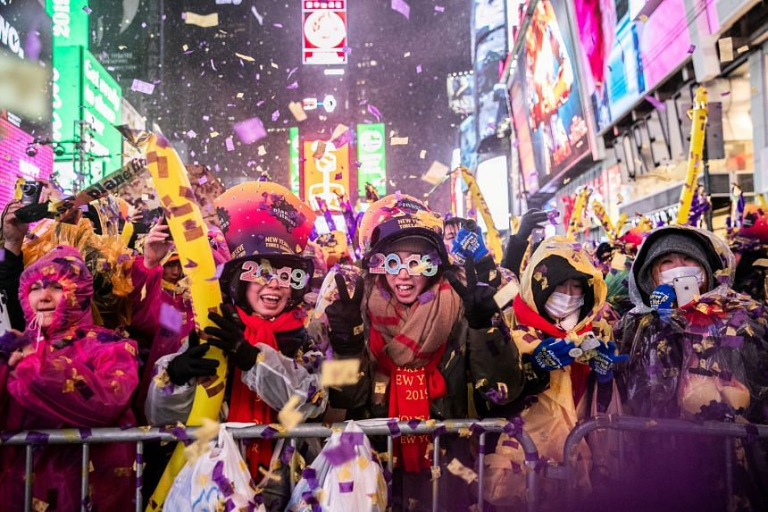 Merrymakers braving the pouring rain to ring in the new year at New York's Times Square amid fireworks and cheer.