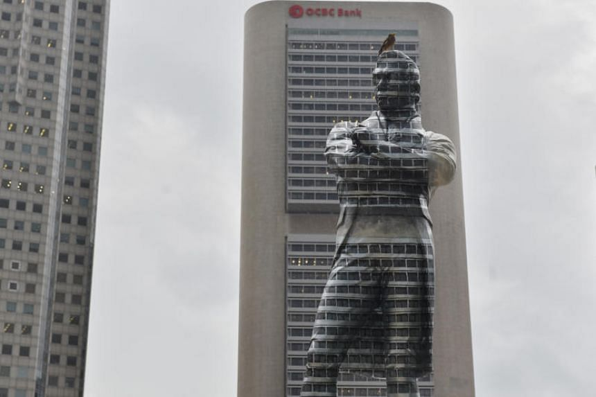 Half of the statue has been covered in dark grey paint, creating an optical illusion.